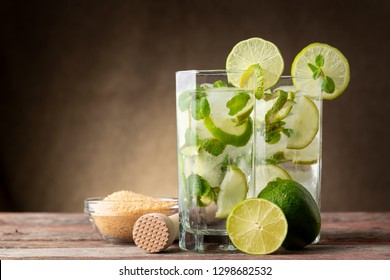 Two mojito cocktails with lots of ice, white rum, lemon juice and tonic, decorated with lime slices and mint leaves on a rustic wooden table