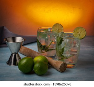Two mojitos with lemons and jigger in orange background