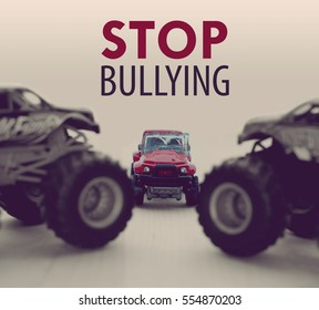 Two Monster Trucks bullying a small car