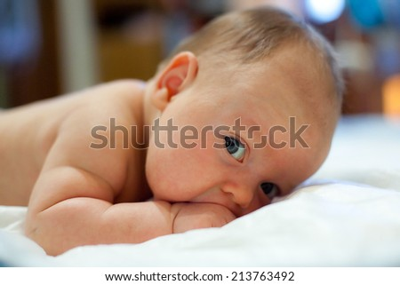 Two Month Old Baby Laying On His Tummying His Fist And Trying To Hold