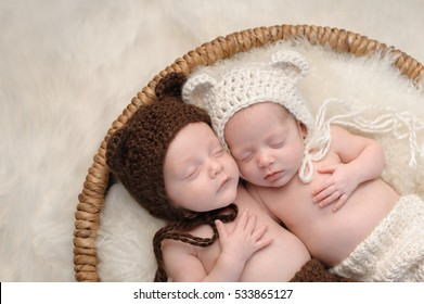 Two month old, boy and girl fraternal twin babies. They are sleeping together in a basket wearing coordinated, crocheted, bear bonnets.