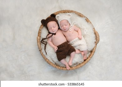 Two month old, boy and girl fraternal twin babies. They are sleeping together in a basket wearing coordinated, crocheted, bear bonnets and shorts.