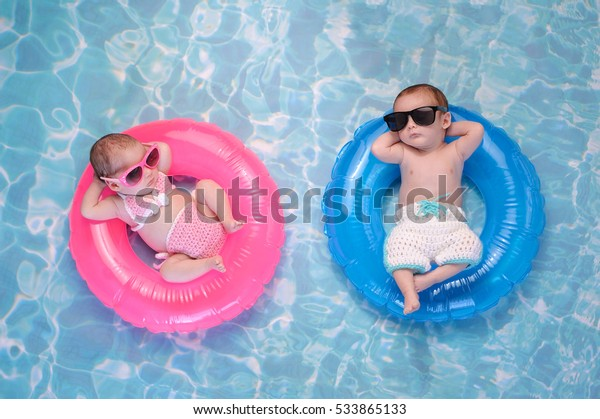 Two month old twin baby sister and brother sleeping on tiny, inflatable, pink and blue swim rings. They are wearing crocheted swimsuits and sunglasses.