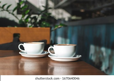 Two morning cups of coffee with nice foam on wooden background