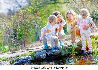 Two mothers laugh while holding their children by a small pond for a walk in the park