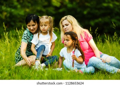 Two mothers and two small daughters in the park