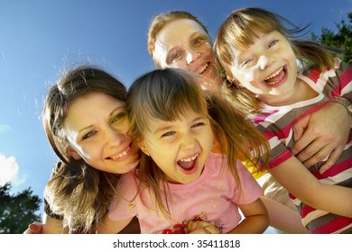 Two mothers with their little daughters smiling and laughing in the park