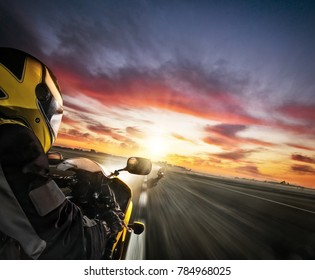 Two motorbike's riders heading to the city. Concept of speed, travel and freedom. Beautiful dramatic sunset sky.