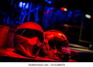 two motorcycle helmets in red neon light