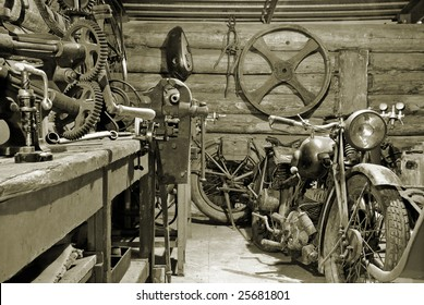 Two motorcycles and tools in old garage.