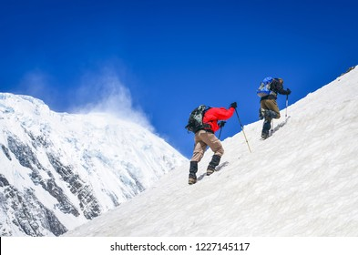 Two mountain backpackers walking on steep hill with snowed peaks background, Himalayas