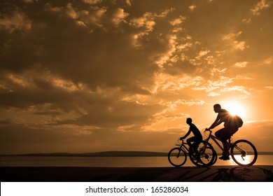 two mountain biker - comantic couple silhouette in sunrise   agains sun set cloudy sky and sea shore background Space for inscription