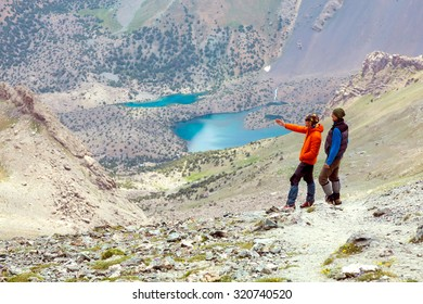 Two Mountain Climbers Staying on Dusty Trail and Discussing Climbing Rout Pointing with Hand Sporty Clothing Mountain Lakes on Background
