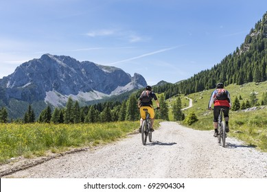 Two mountainbiker on a gravel road on Nassfeld in Carnic Alps with view to mountain Rosskofel