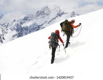two mountaineers with ice ax climbs on the mountain in the background of the landscape of snowy mountains