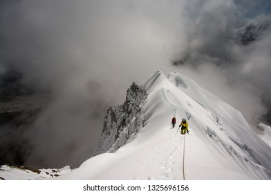 Two mountaineers on a very exposed rigde covered by snow with challenging weather conditions. Lobuche east with a view towards Mount Everest and Ama Dablam