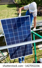 Two mounters installing solar panels on green metallic carcass. Wearing blue uniform, protective helmets. Using special equipment, providing new technologies ecology saving, green energy solution.