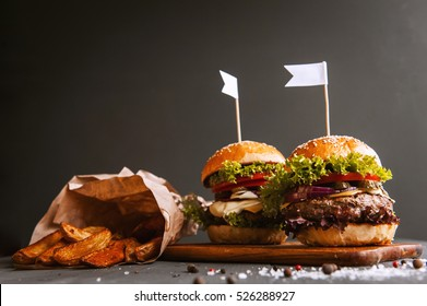 Two mouth-watering, delicious homemade burger used to chop beef.on the wooden table. small white flags inserted in the burgers.
