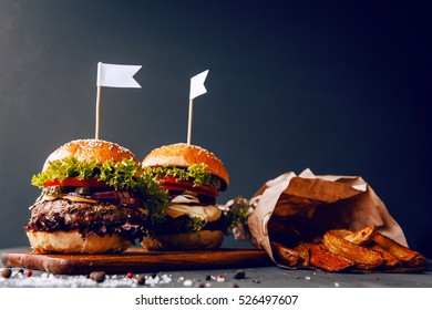 Two mouth-watering, delicious homemade burger used to chop beef. on the wooden table. small white flags inserted in the burgers.