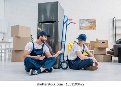 two movers talking while sitting near hand truck, carboard boxes and refrigerator in apartment