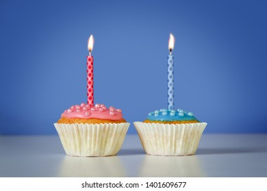 two muffins or cupcakes with pink and blue burning candles against a blue background, birthday concept with copy space