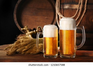 Two mug of beer .With wheat and barley and barrels spikes on bakcground.Still life.Copy space