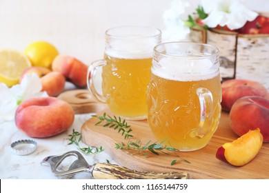 Two mug of light fruit craft beer and fruits