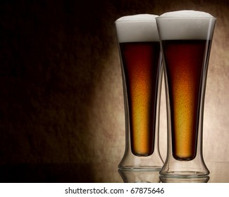two mugs of beer against a stone wall