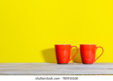 Two mugs of coffee or tea in bold color setting with red on yellow background and shadow