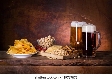 Two mugs of dark and light beer and some snacks in the European style