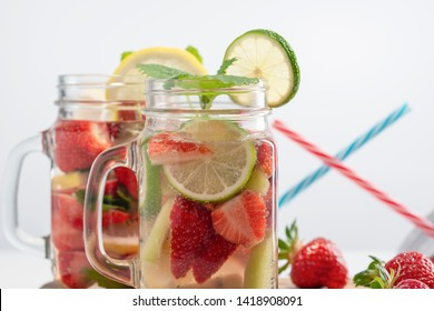 Two mugs of fruit refreshing water made from strawberries, lemon, mint and lime in the background, drinking straws and fresh strawberries