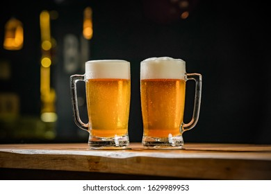 Two mugs full of chopp, one with pilsen chopp and one with dark chop on a rustic table