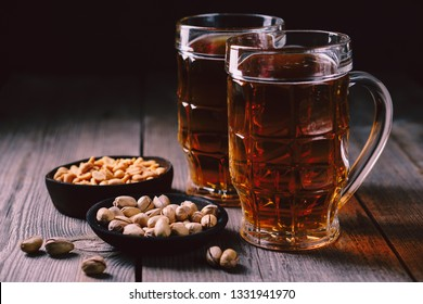 two mugs of lager beer and snacks set. bar table. restaurant, pub, food concept. delicious drink and salty nuts. oktoberfest atmosphere, craft brewery background
