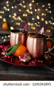 Two mugs of mulled wine with cinnamon and pomegranate