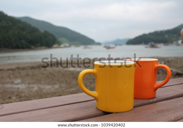 Two mugs on a bench