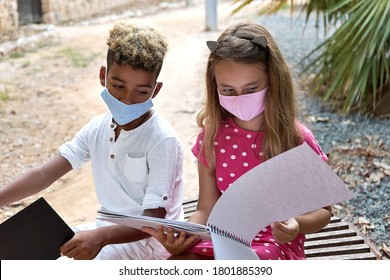 Two multi ethnic adorable 9s 10s years girl and boy sit on bench talking discuss their drawings spend free time together outdoor. Leisure, hobby and pastime. Friendship racial equality amity concept