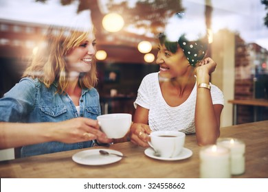 Two multi ethnic friends enjoying coffee together in a coffee shop viewed through glass with reflections as they sit at a table chatting and laughing