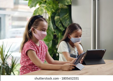 Two multi racial beautiful school age 9s girls sit at desk with portable computer. Using modern device ignoring each other, studying distantly by wireless gadget, new generation tablet overuse concept