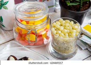 Two Multicolor Jelly Beans Jars on Wooden Table with Other Things