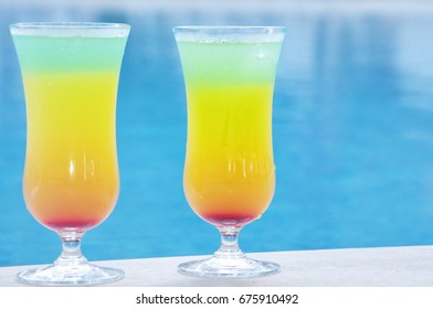 Two multi-colored cocktails on the background of the pool