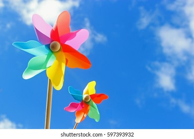 two multicolored pinwheels against blue sky