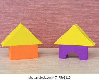 Two multicolored (yellow, purple, orange) house of building blocks (triangle, rectangle), a children educational toy on a pink background.