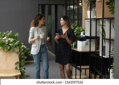 Two multicultural female colleagues enjoying coffee break time, discussing working issues during walk at office. Young vietnamese intern consulting with caucasian female leader at coworking workplace.