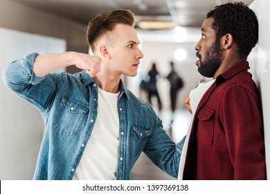 two multicultural students fighting in corridor in college