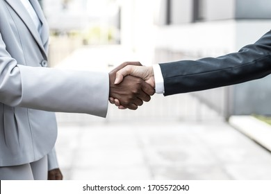Two multiethnic business ladies in suits shaking hands near office building. Business women meeting outside in city. Dealing or communication concept