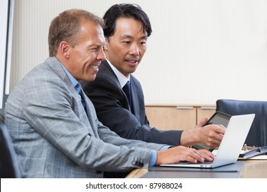 Two multi-ethnic colleagues working together on a computer