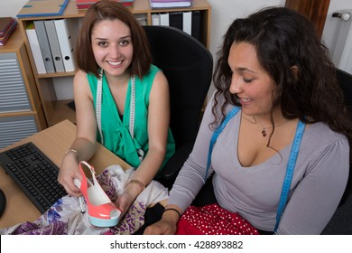 Two multiethnic female fashion designers working at desk