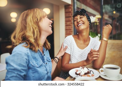 Two multiethnic young female friends enjoying coffee together in a restaurant laughing and joking while touching to display affection