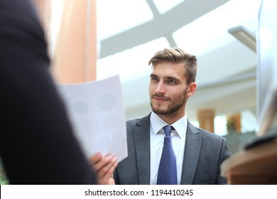 Two multinational young businessmen in suit discussing something and pointing a paper.