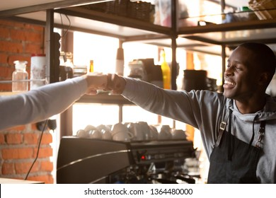 Two multiracial fellows american and caucasian cafe restaurant workers or waiter and public place guest friends greeting each other fist bumping as a symbol of companionship, friendship and solidarity